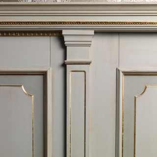 White lacquered boiserie with golden details and columns