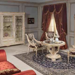 Living room Luigi XVI style: round table with carved chairs, glass showcase and wall mirror. All withe over gold finish, handmade carvings. White and Gold classic luxury furniture collection